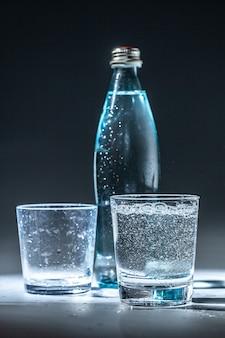 Set da tavola servito con bottiglia di acqua minerale e vetro