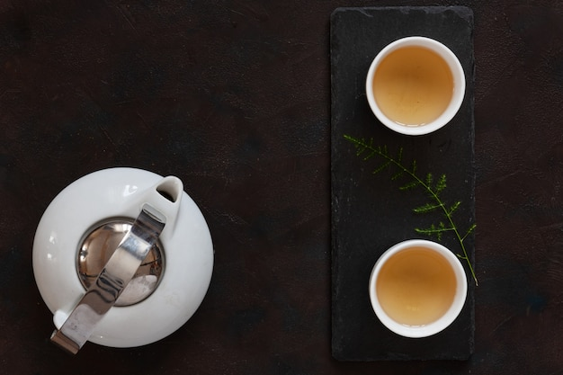 Set da tè asiatico in porcellana bianca con tè verde latte oolong su scrivania in pietra nera