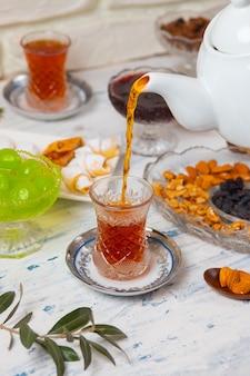 Set da tè con varietà di noci tradizionali, limone, confettura e dolci serviti sulla tovaglia bianca