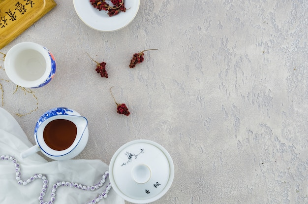 Set da tè in porcellana cinese blu e bianca con erbe su sfondo grigio cemento