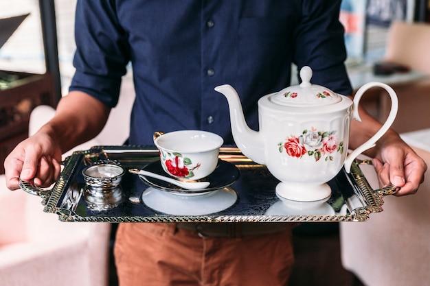 Set da tè inglese vintage in porcellana con teiera, tazza da tè, piatto, cucchiaio e filtro per il tè.