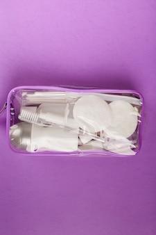 Set da viaggio con piccola bottiglia, in sacchetto trasparente per cosmetici su viola. vista dall'alto
