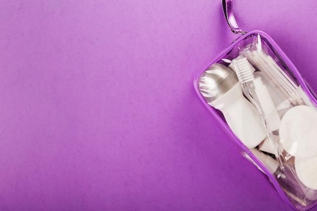 Set da viaggio con piccola bottiglia, in sacchetto trasparente per cosmetici su viola