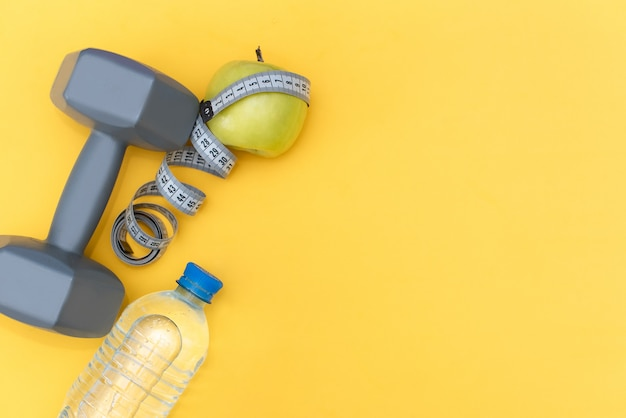 Set dell'atleta con abbigliamento femminile, manubri e bottiglia di acqua su sfondo giallo