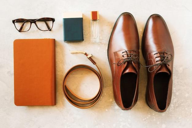 Set di accessori alla moda per uomo su sfondo grigio. piatto disteso di cintura elegante, occhiali, profumo, quaderno. concetto di moda di strada per l'uomo.