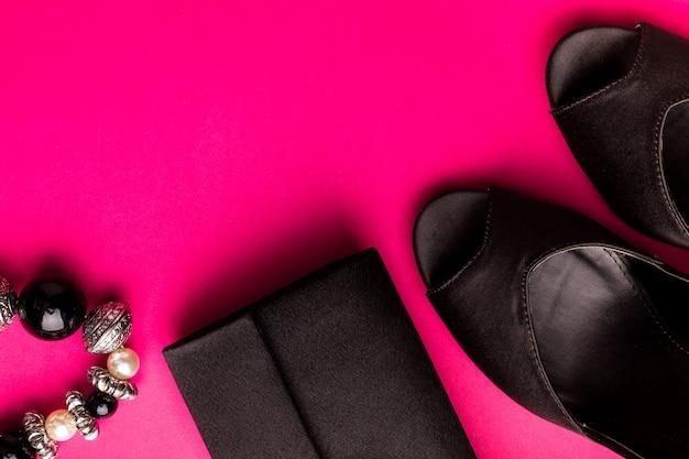 Set di accessori moda donna. nero e rosa minimo. scarpe, braccialetto e borsa neri sul rosa. disteso.
