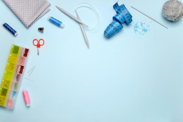Set di accessori per cucire su sfondo blu, vista dall'alto