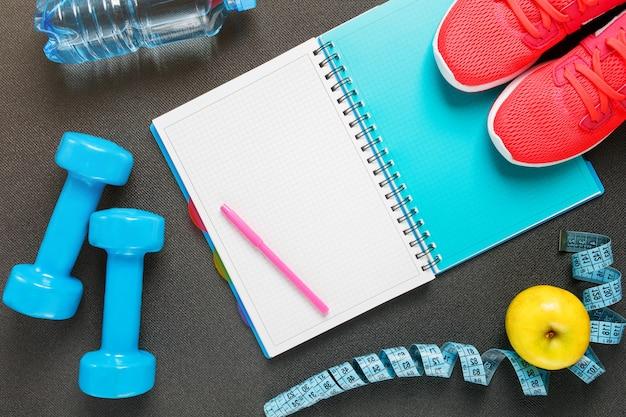 Set di accessori sportivi per il fitness con attrezzi ginnici su grigio