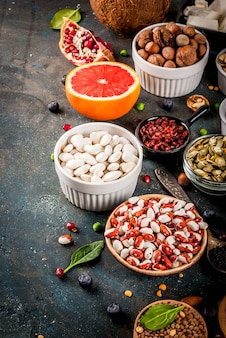 Set di alimenti biologici sani, supercibi - fagioli, legumi, noci, semi, verdure, frutta e verdura. vista superiore dello spazio blu scuro della copia del fondo