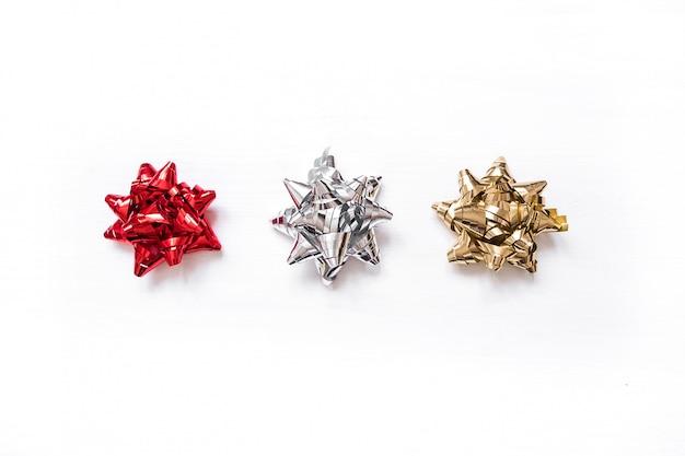 Set di archi di raso nastro rosso, argento e oro isolato su sfondo bianco.