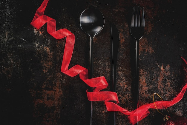 Set di argenteria su una superficie arrugginita scura con nastro rosso