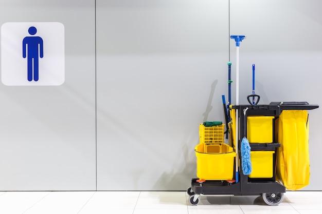 Set di attrezzature per la pulizia e segno di servizi igienici per uomini sul muro in aeroporto
