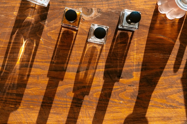 Set di bottiglie di profumo su una luce intensa con le ombre