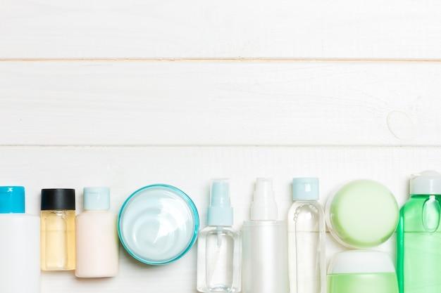 Set di bottiglie e vasetti di crema e cosmetici su legno. cura del corpo con spazio vuoto r