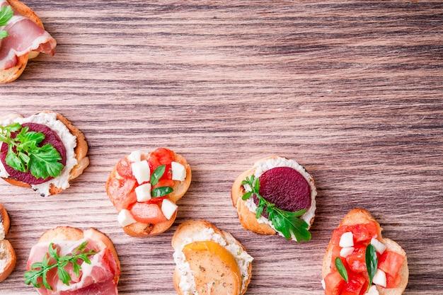 Set di bruschette su tavola di legno. cibo italiano. vista dall'alto, cornice, copyspace.