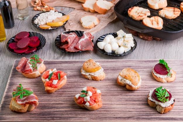 Set di bruschette su tavola di legno.grediente per crostini. cibo italiano.