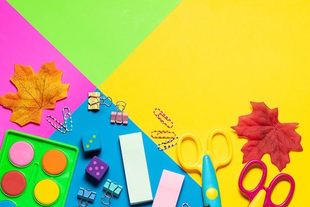 Set di cancelleria luminoso, spray antisettico e maschere facciali protettive su vista dall'alto di sfondo multicolore.