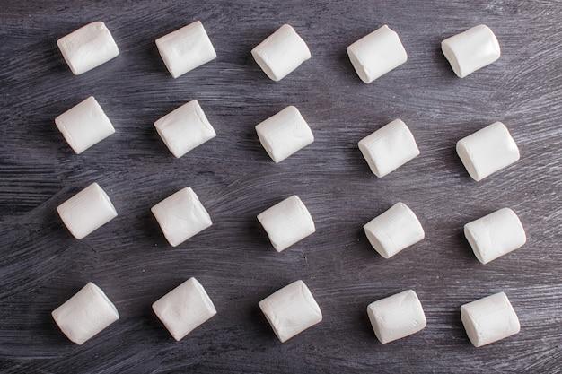 Set di caramelle gommosa e molle su fondo di legno nero. motivo geometrico.