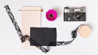 Set di carte vicino fiore fresco con anelli sul piatto, retro macchina fotografica e nastro
