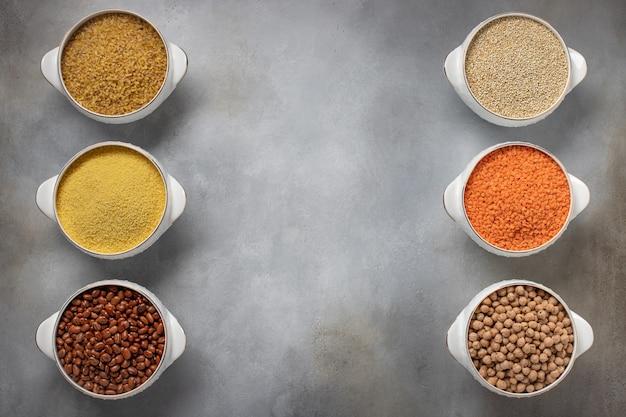 Set di cereali per alimenti crudi (bulgur, couscous, fagioli, quinoa, lenticchie, ceci), cornice per testo superficie grigia