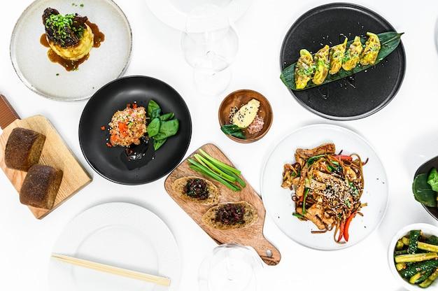 Set di cibo cinese assortito. tagliatelle, riso fritto, gnocchi, anatra alla pechinese, dim sum, involtini primavera. piatti famosi sul tavolo. sfondo grigio. vista dall'alto.