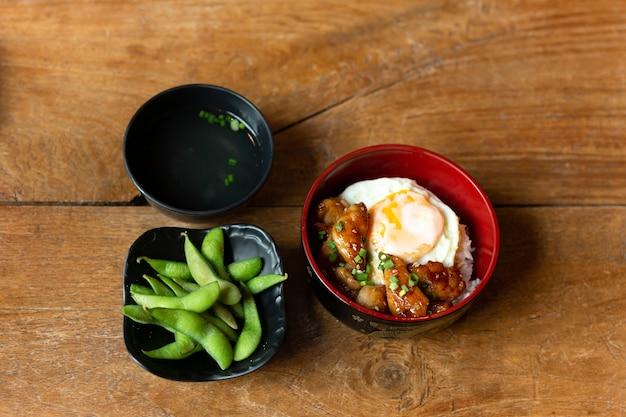 Set di cibo giapponese di pollo teriyaki con riso e uovo fritto in una ciotola.