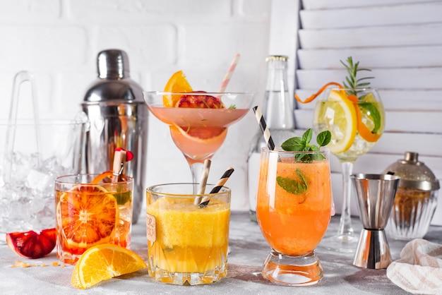 Set di classici cocktail di gin tonic all'arancia, con lime e foglie di menta nei bicchieri