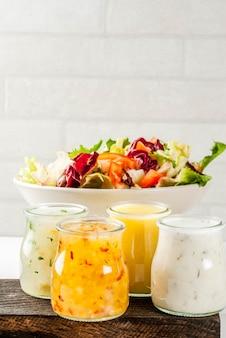 Set di condimenti per insalata classici senape di miele, ranch, vinaigrette, limone e olio d'oliva, sul tavolo di marmo bianco,