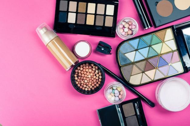Set di cosmetici colorati sul tavolo rosa