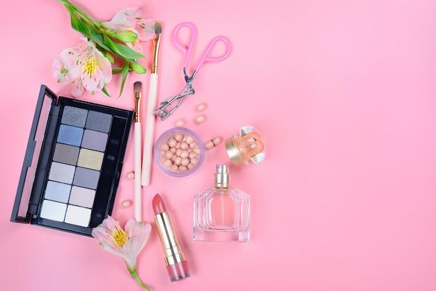Set di cosmetici decorativi con pennelli trucco su sfondo rosa
