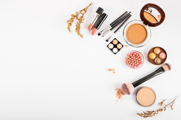 Set di cosmetici decorativi e pennelli trucco su sfondo bianco