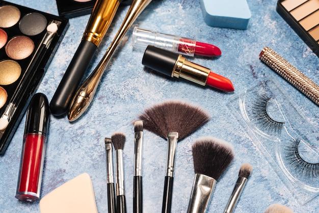 Set di cosmetici decorativi, pennelli trucco sull'azzurro