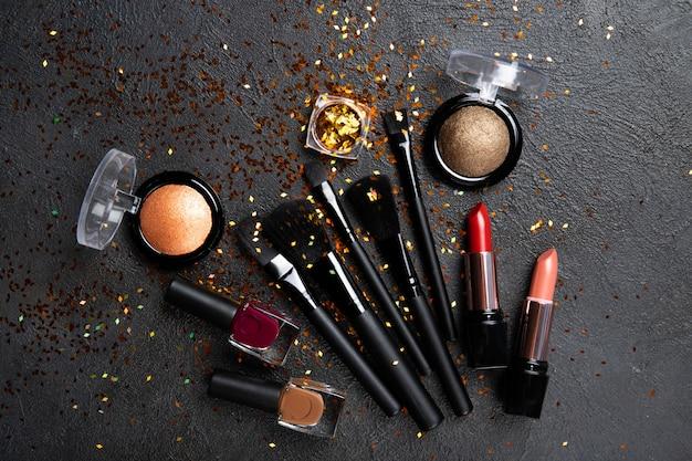 Set di cosmetici decorativi su una parete nera.