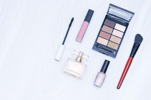 Set di cosmetici per il trucco (pennelli, ombre). componga gli elementi essenziali nudi su fondo di legno bianco. piatto disteso, copia spazio, concetto di blog.