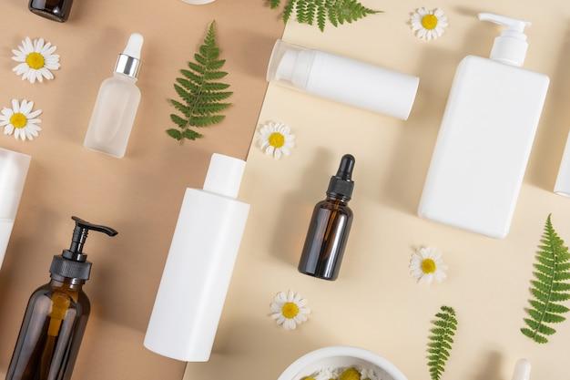Set di cosmetici per la cura. varie bottiglie, tubi con cosmetici, fiori di camomilla, foglie di felce su un beige
