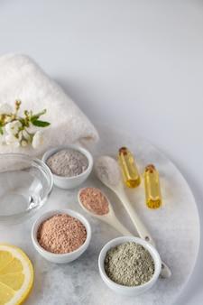 Set di diverse polveri di fango cosmetico argilla sulla superficie bianca. ingredienti per maschera o scrub viso e corpo fatti in casa e rametto fresco di fioritura di ciliegie. spa e concetto di cura del corpo.