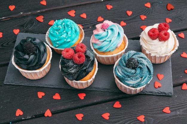 Set di diversi deliziosi cupcakes sul buio