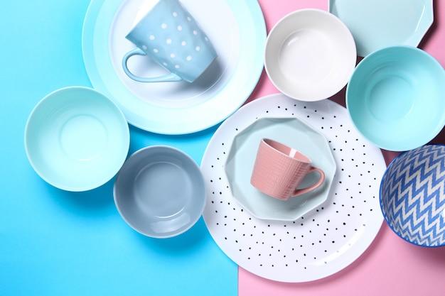 Set di diversi piatti bianchi e blu moderni, ciotole e tazze su rosa e blu.