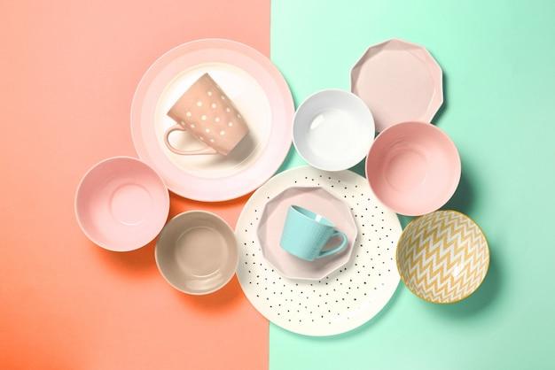 Set di diversi piatti moderni, ciotole e tazze su arancione e verde.