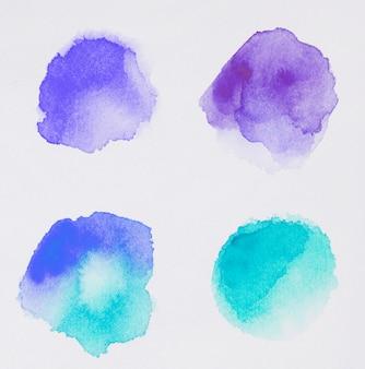 Set di diversi toni di vernici blu su carta bianca