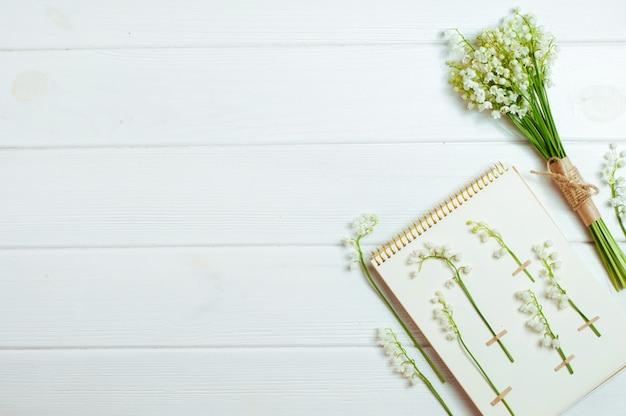 Set di erbario con mughetti, bouquet di fiori su fondo di legno bianco