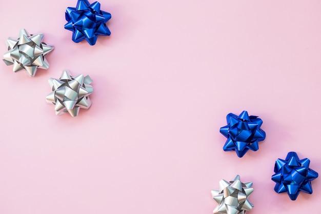 Set di fiocchi d'argento e blu su sfondo rosa