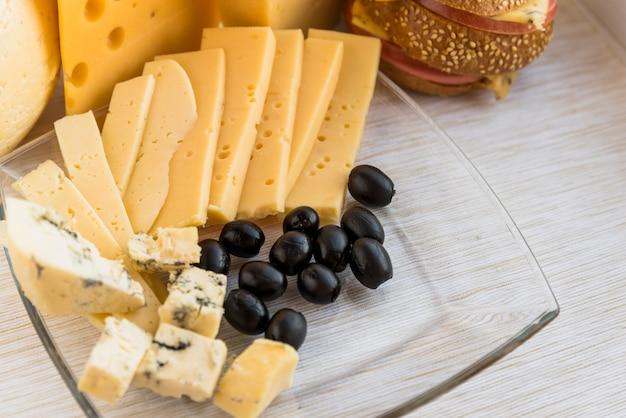Set di formaggio fresco e olive sul piatto vicino al panino