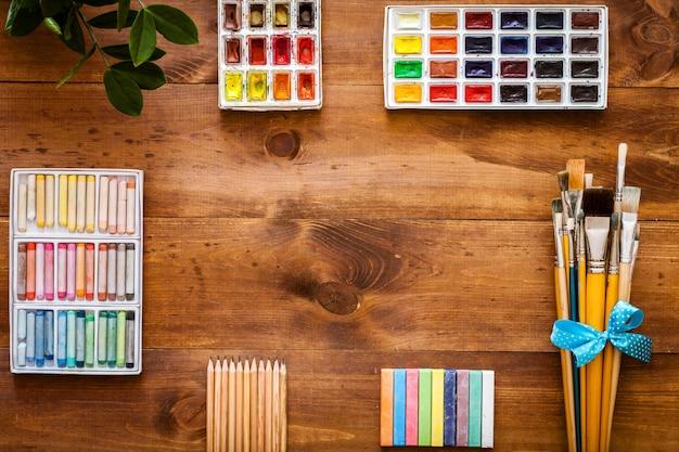 Set di forniture di strumenti di accessori di lavoro creativo di art design, pennelli, paintbox con acquerelli, pastelli, matite su fondo artistico in legno marrone, torna a scuola. vista dall'alto, disteso, copia spazio