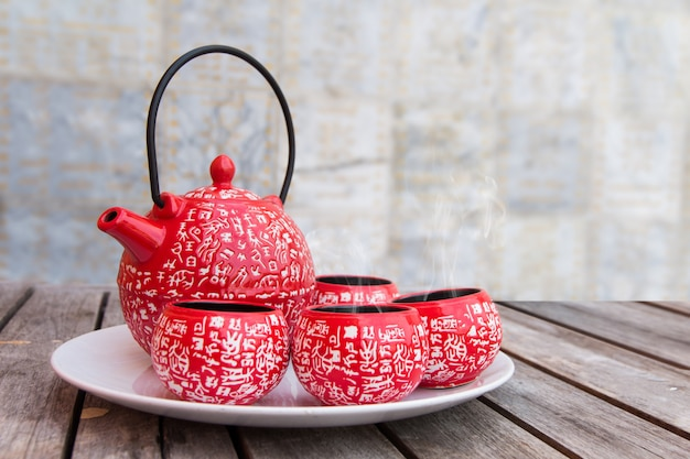 Set di freni per il tè, tazze rosse di tè caldo sul tavolo di legno