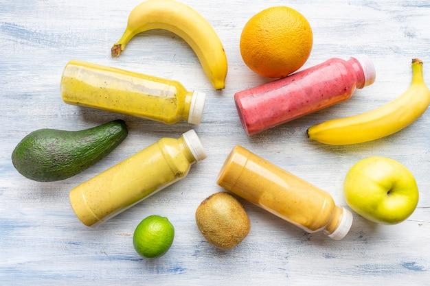 Set di frullati multicolori in bottiglie in composizione con banana, kiwi, lime, avocado su un fondo di legno blu.