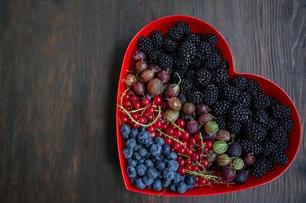 Set di frutta fresca more, uva spina, ribes rosso, mirtilli in una scatola di cuore rosso