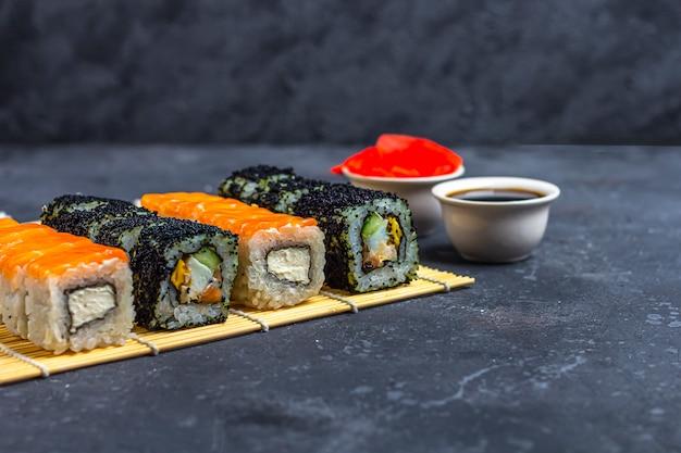 Set di involtini di sushi con salmone e frittata, tofu e verdure, uova di pesce volante, tempura su makisu su un tavolo scuro. cibo tradizionale giapponese.