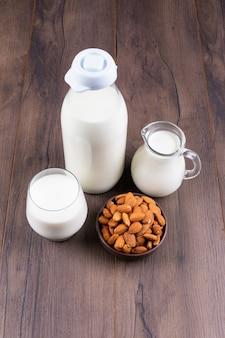 Set di latte e mandorle su un tavolo scuro e in legno. veduta dall'alto.