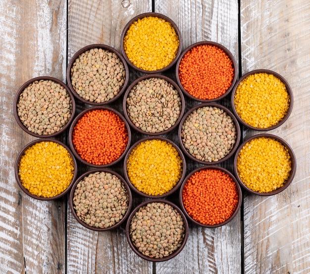 Set di lenticchie rosse, gialle, verdi e lenticchie diverse in ciotole marroni su un tavolo di legno beige. vista dall'alto.